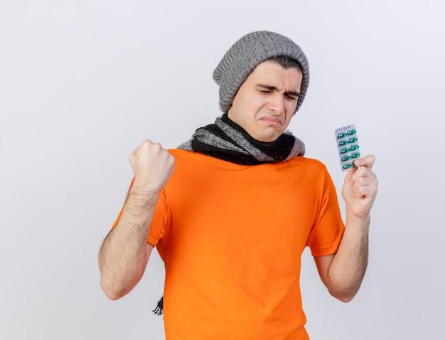 Con gli occhi chiusi giovane uomo malato che indossa il cappello invernale con sciarpa tenendo le pillole e mostrando sì gesto isolato su bianco