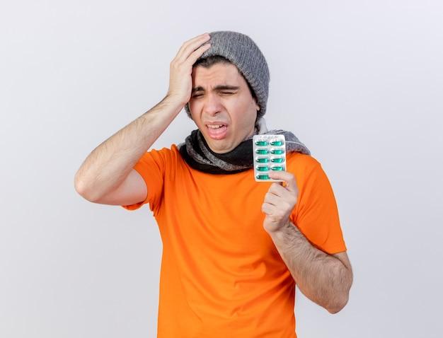 Con gli occhi chiusi giovane uomo malato che indossa il cappello invernale con la sciarpa che tiene le pillole