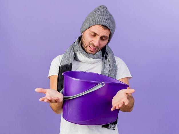 目を閉じて、プラスチック製のバケツを保持し、紫色の背景で隔離のカメラで手を差し伸べるスカーフと冬の帽子をかぶって若い病気の男