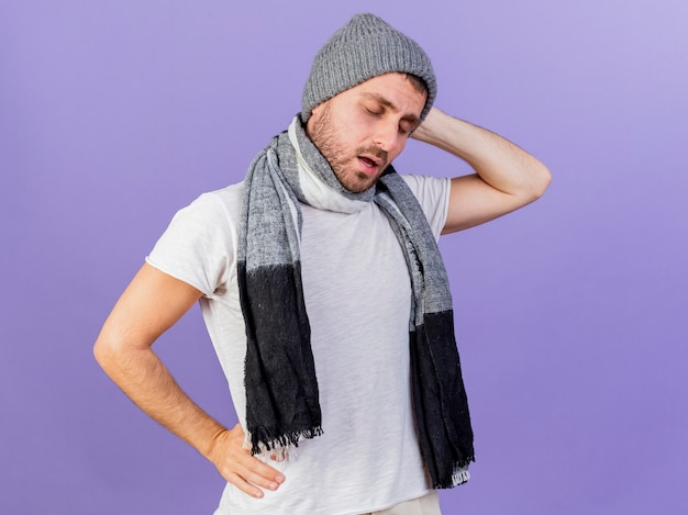 With closed eyes young ill man wearing winter hat with scarf putting hands on head and hip isolated on purple background