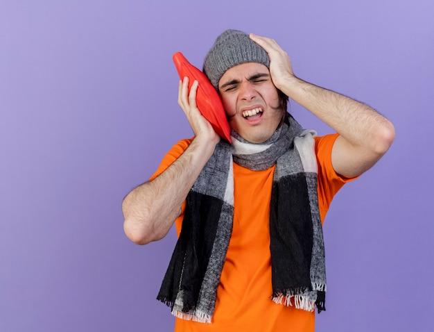 Con gli occhi chiusi giovane uomo malato che indossa cappello invernale con sciarpa mettendo la borsa dell'acqua calda sulla guancia mettendo la mano sulla testa dolorante isolato su sfondo viola