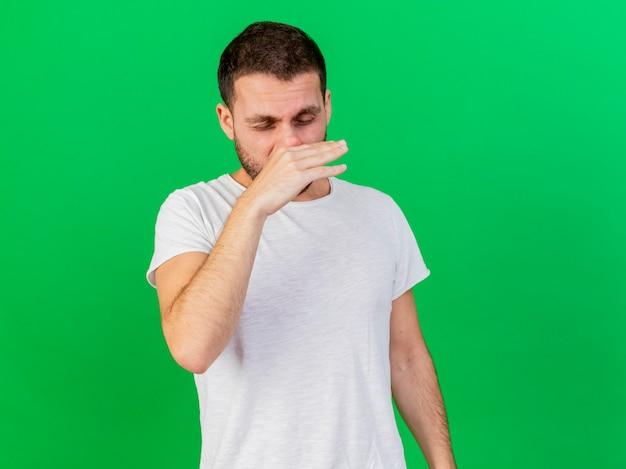 Con gli occhi chiusi giovane uomo malato asciugandosi il naso con la mano isolata su sfondo verde