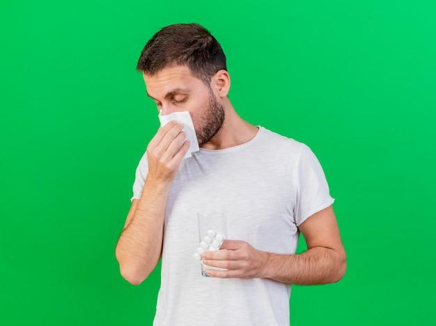 Con gli occhi chiusi giovane uomo malato pulendosi il naso con il tovagliolo e tenendo le pillole con un bicchiere d'acqua isolato su sfondo verde