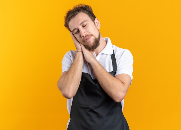 目を閉じて、黄色の背景に分離された睡眠ジェスチャーを示す制服を着た若い男性理髪師