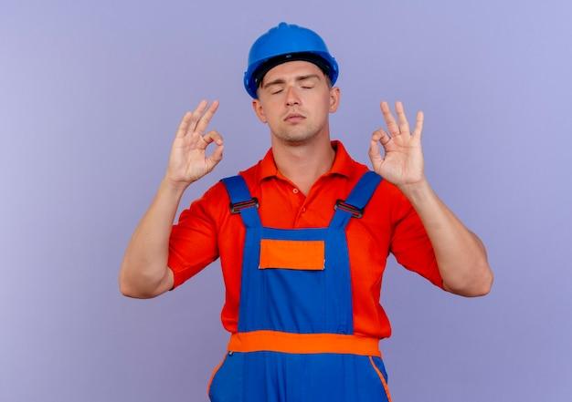 Con gli occhi chiusi giovane costruttore maschio che indossa l'uniforme e il casco di sicurezza che mostra il gesto okey sulla porpora