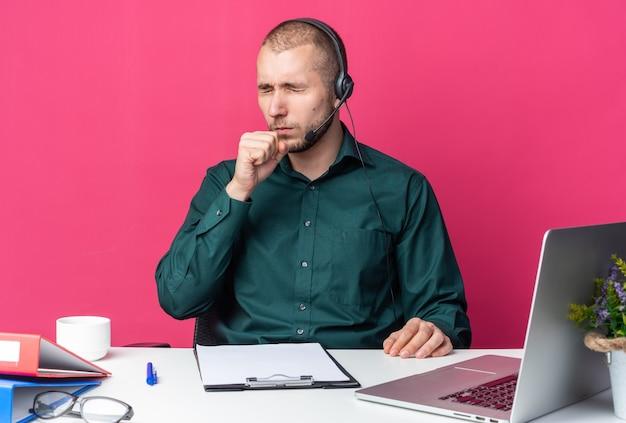 닫힌 눈으로 사무실 도구 기침과 함께 책상에 앉아 헤드셋을 착용하는 젊은 남성 콜 센터 교환원