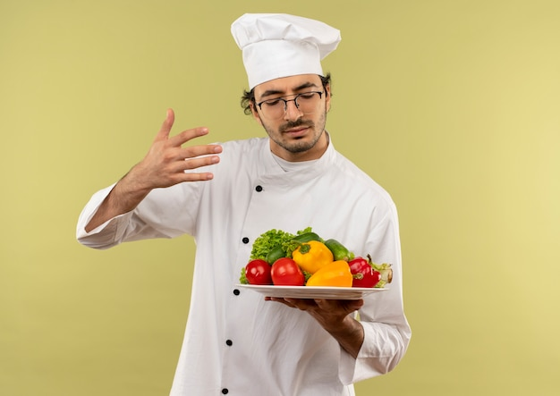 目を閉じて、若い男性料理人がシェフの制服を着て、緑の壁に隔離されたプレートに野菜を保持し、嗅ぐ眼鏡をかけます