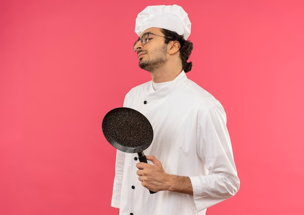 With closed eyes young male cook wearing chef uniform and glasses holding frying pan on pink