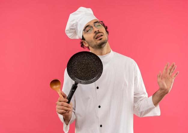 Con gli occhi chiusi giovane cuoco maschio che indossa l'uniforme del cuoco unico e vetri che tengono la padella con il cucchiaio e il cucchiaio della mano sparsi sul colore rosa