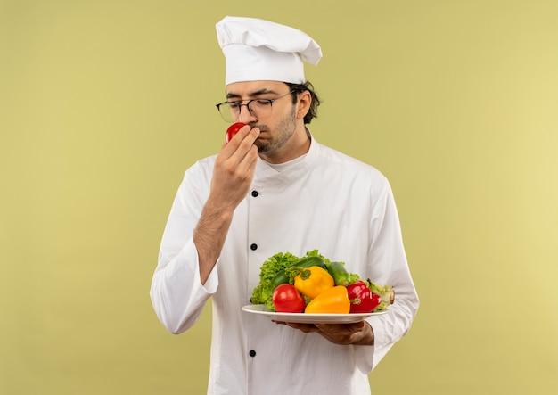 Con gli occhi chiusi giovane cuoco maschio che indossa l'uniforme dello chef e bicchieri tenendo le verdure sul piatto e annusando il pomodoro in mano isolato sulla parete verde con lo spazio della copia
