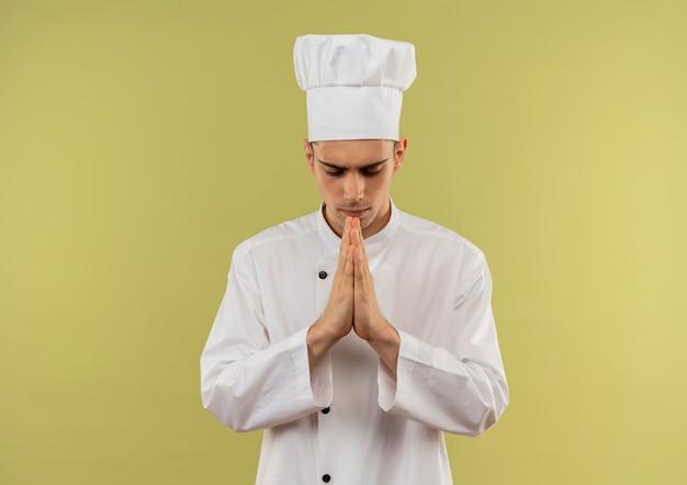 Con gli occhi chiusi giovane cuoco maschio che indossa l'uniforme del cuoco unico che mostra pregare il gesto con lo spazio della copia