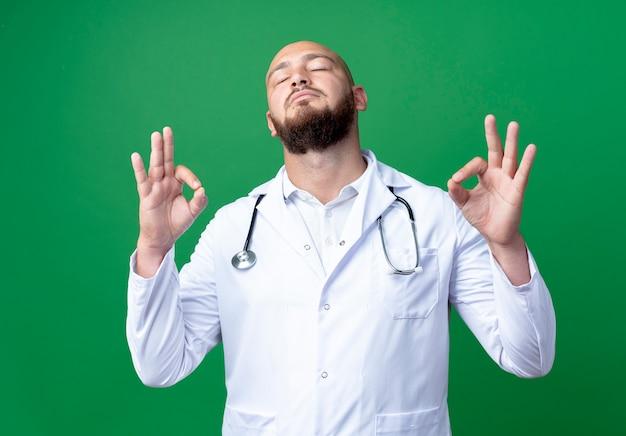 닫힌 된 눈으로 젊은 남성 의사 의료 가운과 녹색에 고립 좋아요 제스처를 보여주는 청진기를 착용