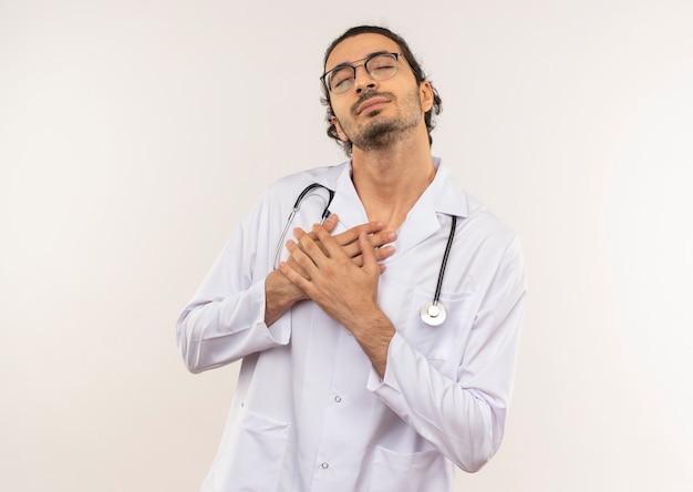 目を閉じて、聴診器で白いローブを身に着けている光学眼鏡をかけた若い男性医師は、コピースペースのある孤立した白い壁に心臓に手を置きます