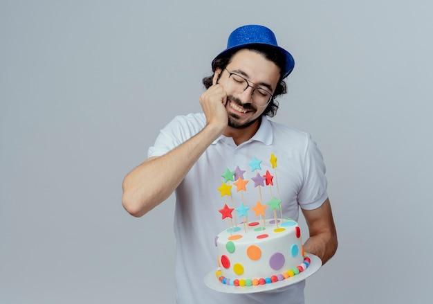 С закрытыми глазами, улыбающийся красивый мужчина в очках и синей шляпе, держащий торт и положивший руку под подбородок, изолированный на белом