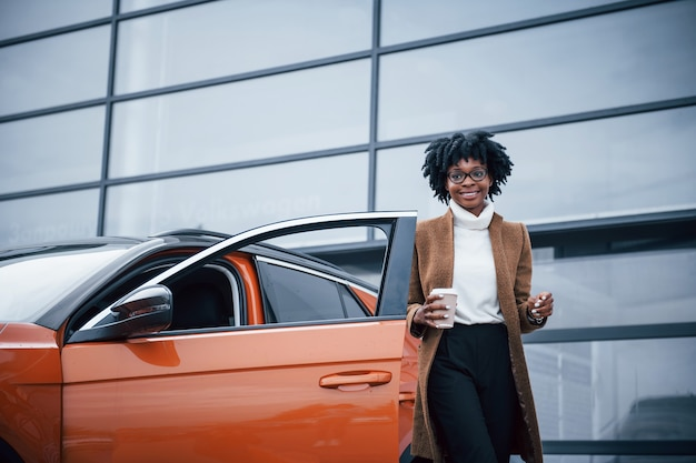 With cup of drink. young african american woman in glasses stands outdoors near modern car.
