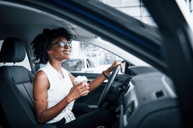 With cup of drink. young african american woman sits inside of new modern car.
