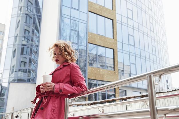 巻き毛付き。暖かい赤いコートを着た大人のきれいな女性が彼女の週末の時間に街を歩いている