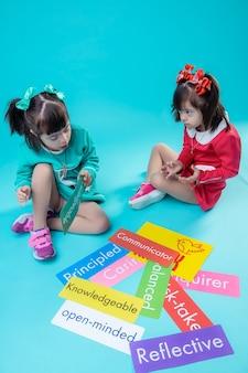 異なるネームプレート付き。タブレットを近くに置いて床に座って一緒に時間を過ごす短い髪の少女