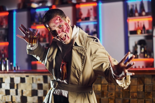 With drink in hand. portrait of man that is on the thematic halloween party in zombie makeup and costume.