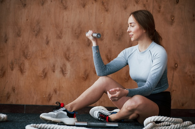 With dumbbell. sportive young woman have fitness day in the gym at morning time