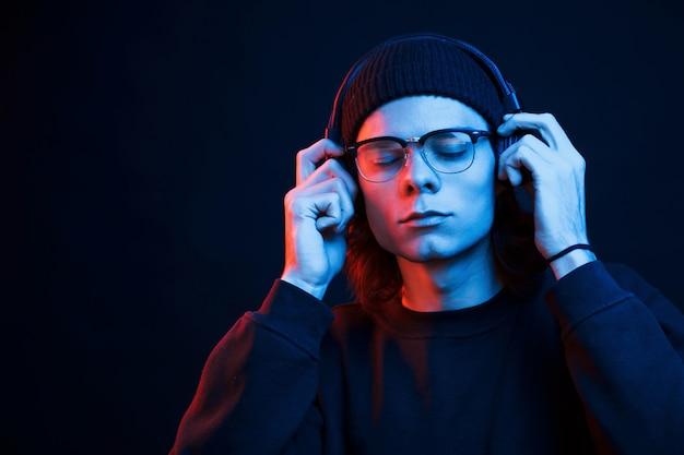 С закрытыми глазами. студия снята в темной студии с неоновым светом. портрет серьезного мужчины.
