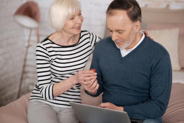 큰 사랑으로. 웃는 수석 여자는 침대에 앉아있는 동안 노트북을 사용하는 그녀의 남편에게 몇 가지 치료를주고 있습니다.