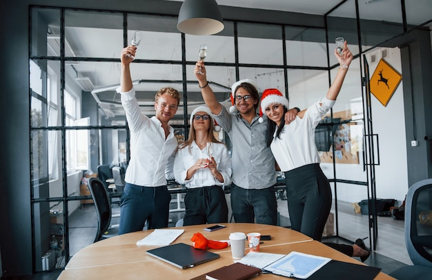 With hands up. employees in formal clothes, glasses with champagne and in christmas hats celebrating new year in the office.