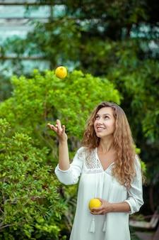 レモン入り。木の近くに立って、レモンを投げる白いドレスの女性