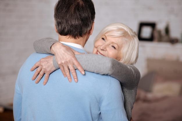 愛を込めて。家で彼女の愛する夫を抱きしめる幸せな老婦人の肖像画。