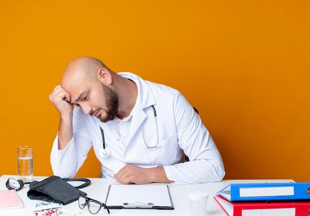 オレンジ色の背景に分離された医療ツールで作業机に座って医療ローブと聴診器を身に着けている頭を下げた悲しい若いハゲ男性医師