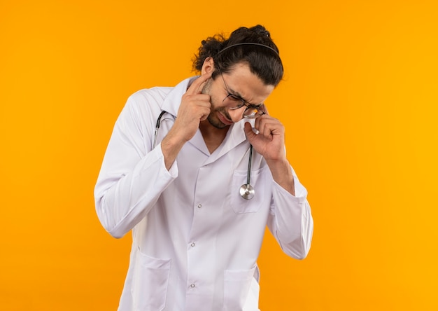 청진 기 의료 가운을 입고 의료 안경 낮은 머리 젊은 의사와 격리 된 노란색 벽 복사 공간에 귀를 폐쇄