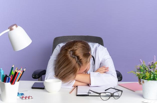 Con la testa abbassata, una giovane dottoressa che indossa una tunica medica con uno stetoscopio si siede al tavolo con strumenti medici isolati su sfondo blu