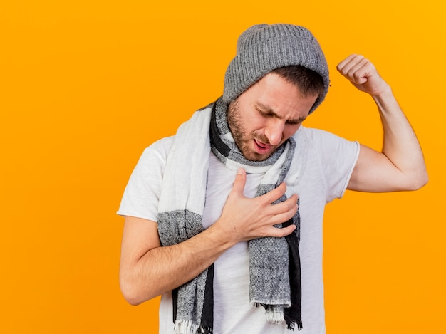 Con la testa abbassata giovane uomo malato che indossa cappello invernale e sciarpa che mostra un forte gesto mettendo la mano sul cuore isolato su sfondo giallo