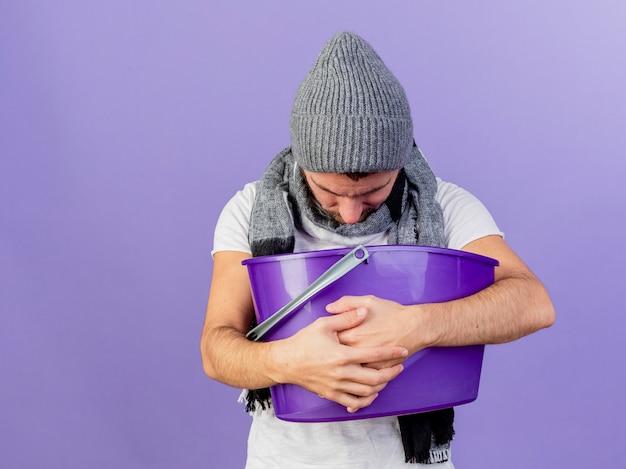 Con la testa abbassata giovane uomo malato che indossa un cappello invernale con sciarpa che tiene cestino di plastica e vomito in esso isolato su sfondo viola