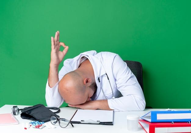 책상에 앉아 의료 가운과 청진기를 입고 낮춘 머리 젊은 남성 의사와