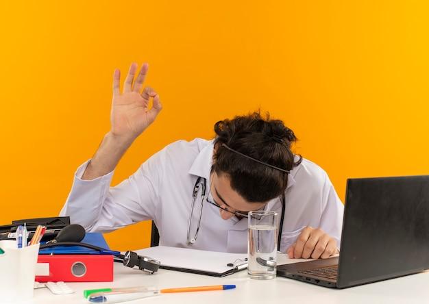 책상에 앉아 청진기와 의료 가운을 입고 의료 안경을 낮추고 머리 젊은 남성 의사와