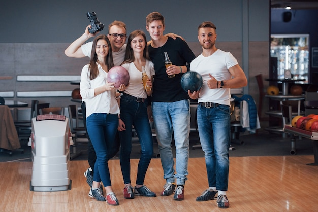 Con il fotografo. i giovani amici allegri si divertono al bowling durante i fine settimana