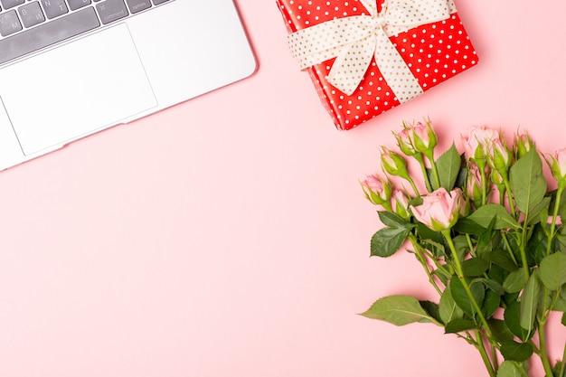 ピンクのバラとgifボックス付き。シンプルなフラット横たわっていた、ピンクの背景。