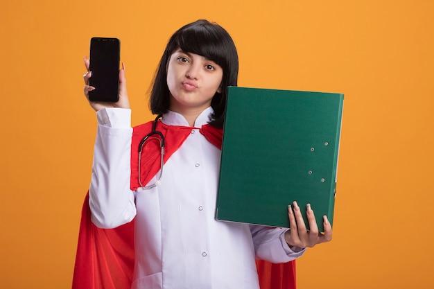 숨이 차서 뺨을 가진 젊은 슈퍼 히어로 소녀 의료 가운과 오렌지에 고립 된 폴더와 전화를 들고 망토 청진기를 입고
