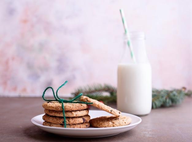 쇼트 브레드와 초콜릿 조각, 튜브가 달린 유리 용기에 신선한 우유가 들어 있습니다. 크리스마스 트리 나뭇 가지, 텍스트 배치