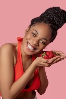 いちご付き。彼女の手でイチゴを保持しているオレンジ色のトップのムラート