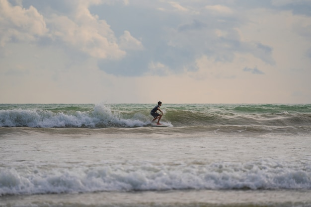 A with a surf in his hands on the sea shore