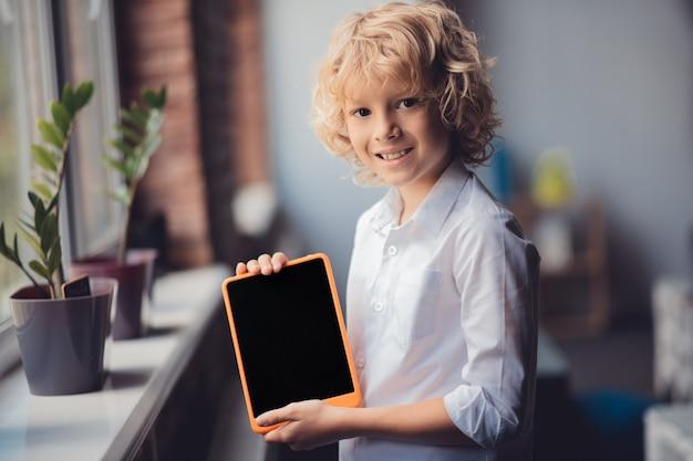 タブレット付き。彼のタブレットを示すと笑顔のかわいい金髪の少年