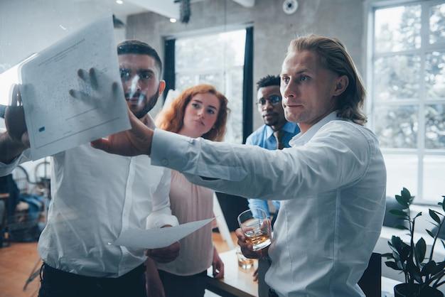С виски в руках. молодая многорасовая команда в официальной одежде в офисе, глядя на прайс-лист