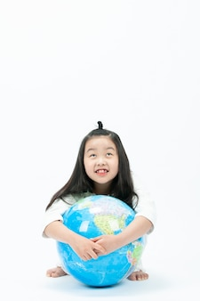 With a white , the child is sitting on a globe and looking at something.