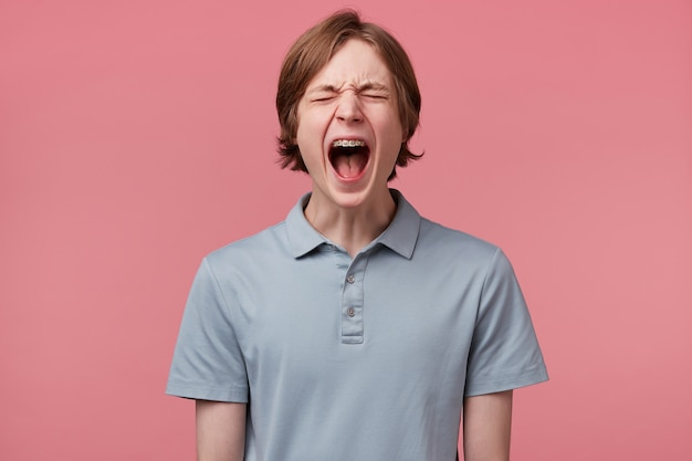 With young man happened something terrific, screams in pain, shouts loudly with wide opened mouth, eyes closed, over pink background. people, negative reaction and feelings concept.