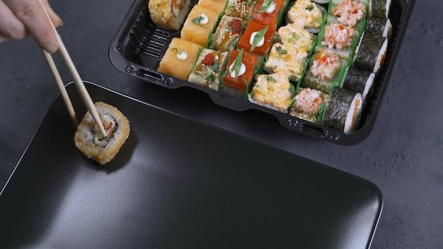 黒いテーブルの上の黒い石のトレイにわさびと生with入りの寿司。上面図