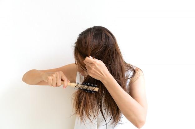 櫛、細い髪のwithでお風呂の後彼女の濡れた汚い髪をブラッシングの女性。髪の損傷、健康と美容のコンセプト。