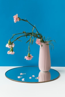 光沢のあるトレイのピンクの花瓶に枯れたピンクのカーネーション