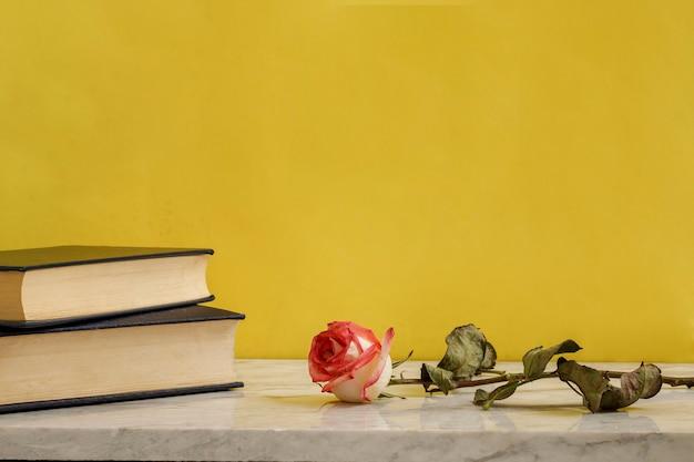 대리석 테이블에 있는 일부 책 옆에 시든 장미 인테리어 장식 개념